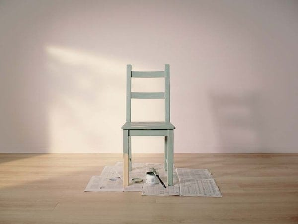 A solid wood chair half painted, sitting on an open newspaper with an open paint can and brush
