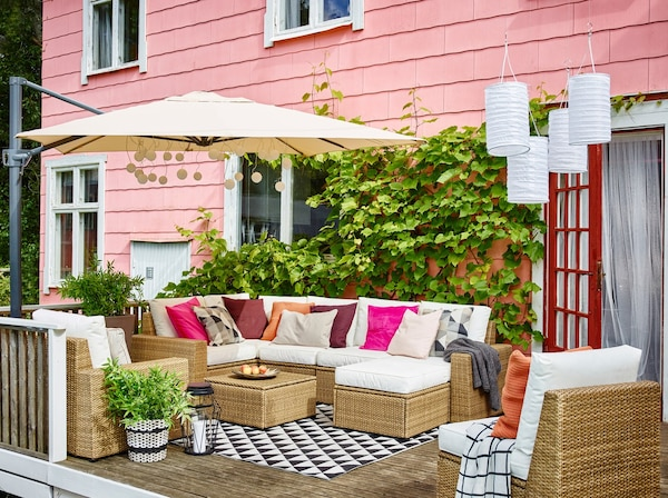 A SOLLERÖN outdoor corner sofa, armchair and footstool and white KUNGSÖ cushions arranged under a large parasol.
