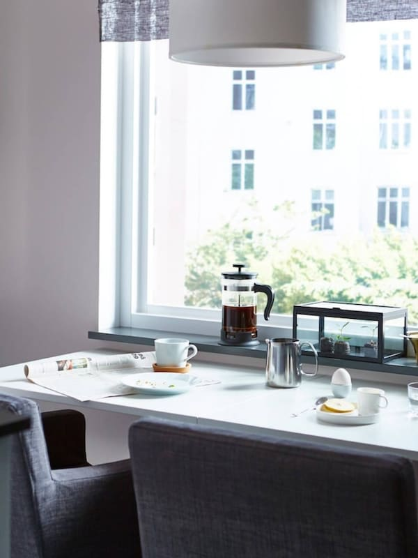 A space-saving dining table, prepared with breakfast, with two dining chairs facing a window.