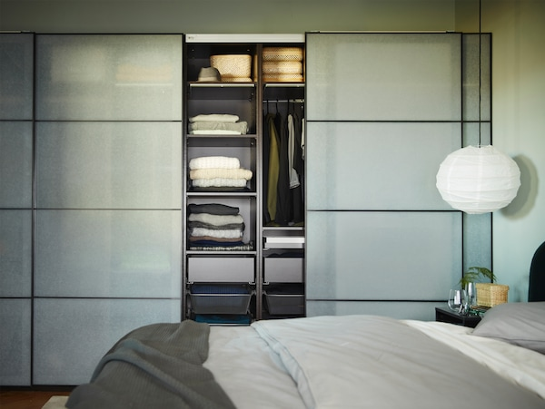 A spacious and slightly open wardrobe in black-brown/white paper effect, a white pendant lamp and a bed with grey bedding.