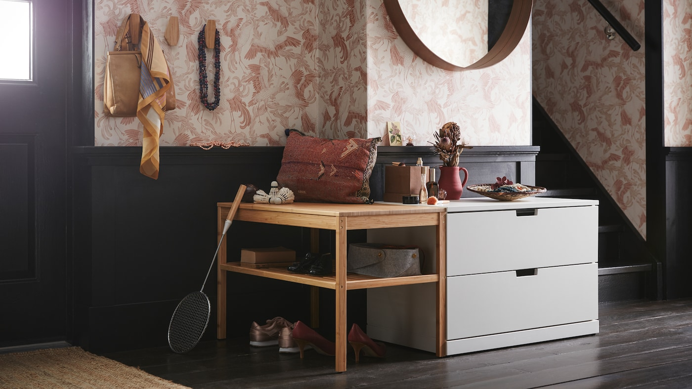 A spacious, floral-wallpaper hallway with a chest of drawers under a round mirror beside a wooden bench with open shelves.
