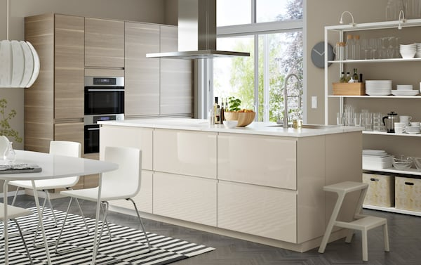 A spacious kitchen with light beige high gloss kitchen doors combined with wooden walnut kitchen doors with in the middle a cooking island with open and closed storage space
