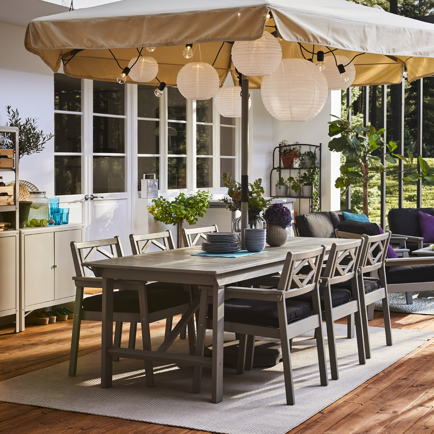 A spacious patio with a table and chairs with armrests in grey, a large parasol, round pendant lamps and a wooden floor deck.