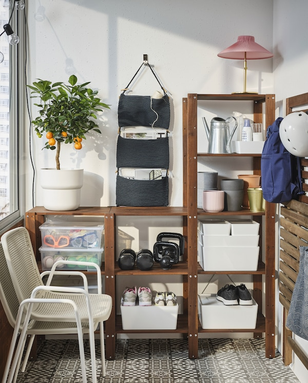 A spacious wooden shelving unit where storage boxes, plant pots, shoes and more are stored. Two stacked chairs in front.