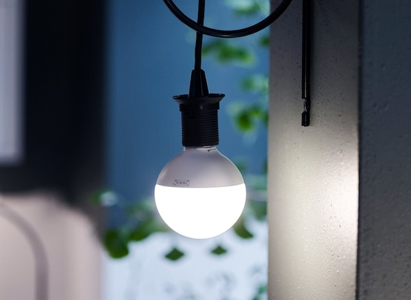 A spherical LED light bulb hanging from a black cord against a dark blue wall.