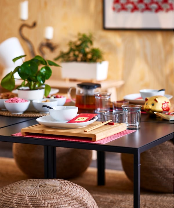 A square RIMFORSA chopping board in bamboo used as an Asian style placemat, on a black table.