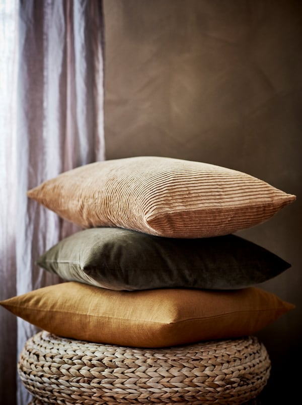 A stack of cushions, including ones in ÅSVEIG and VIGDIS covers, in earthy shades and resting on a woven banana-fiber stool.