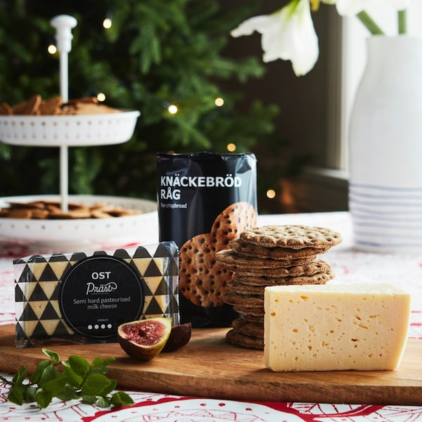 A stack of KNÄCKEBRÖD RÅG rye crispbreads and a block of OST PRAST cheese sit on a wooden chopping board in a festive setting.