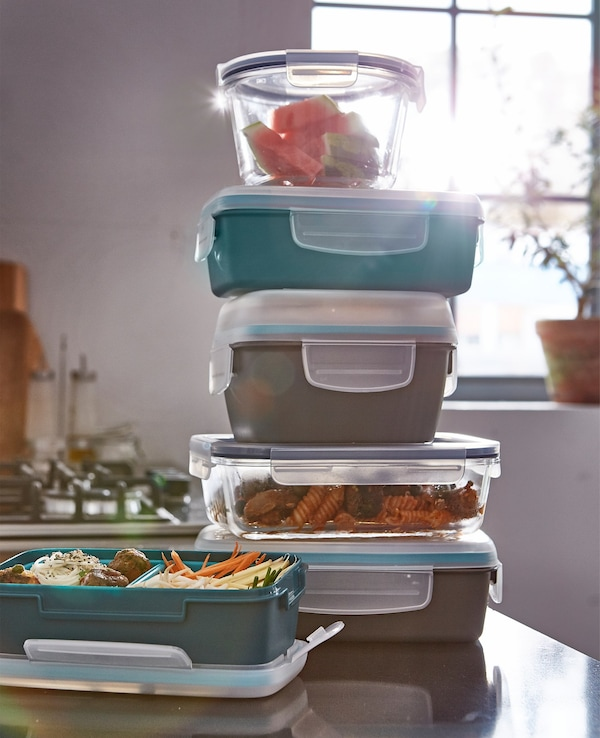 A stack of lunch boxes filled with food on a table.