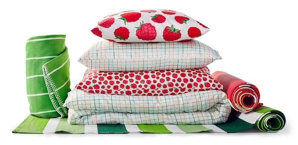A stack of pillows, duvets, towels and rugs.