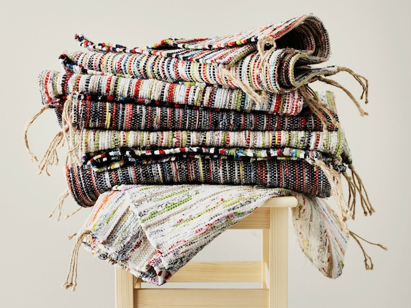 A stack of rugs in various speckled color patterns on a wooden stool with a neutral background.