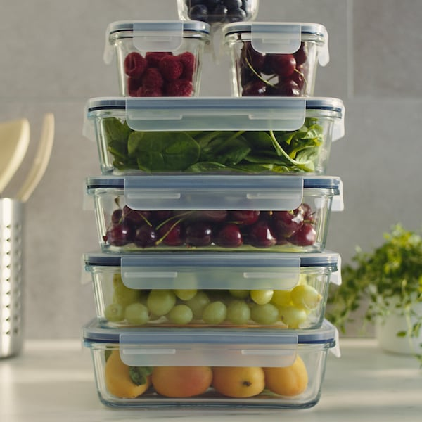 A stack of several food containers of different-sizes, with fruits and vegetables inside.