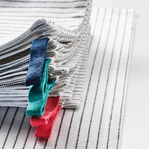 A stack of six, GRUPPERA napkins in white/black with the hanging loops in green, blue and red in the foreground.