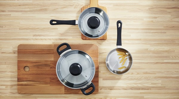 A stainless steel ANNONS 5-piece cookware set on a wooden surface.