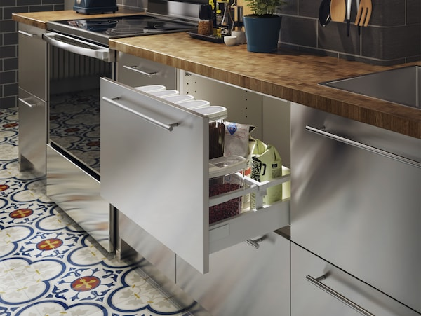 A stainless steel kitchen with a wood worktop in oak/veneer. One drawer is open, and lots of dry goods are stored inside.