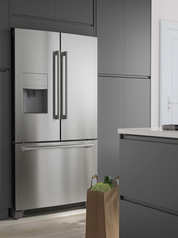A stainless steel refrigerator with gray cabinets surrounding it.