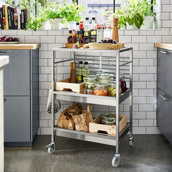 A stainless steel trolley on castors stands by a window. Oils, avocados and pickled vegetables are on the trolley shelves.