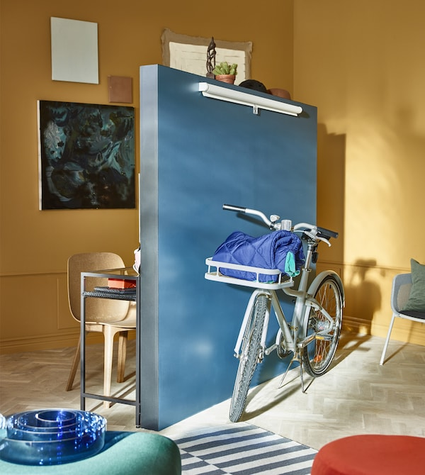 A stand-alone wall sits in the middle of a living room, with a bicycle placed in front of it.