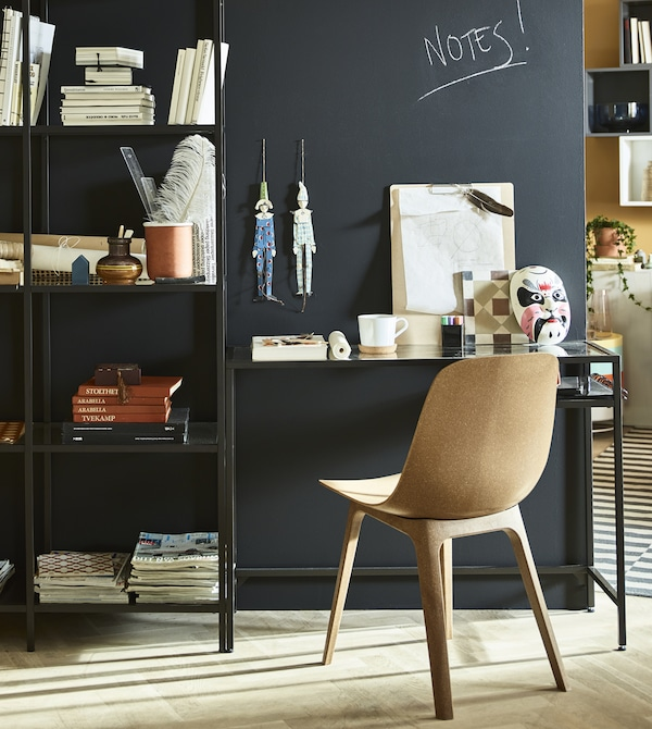 A stand-alone wall with a workspace sits in teh middle of a living room.
