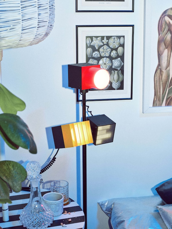 A stand with a red spotlight at the top and a yellow and black speaker connected to in a room with framed wall art.
