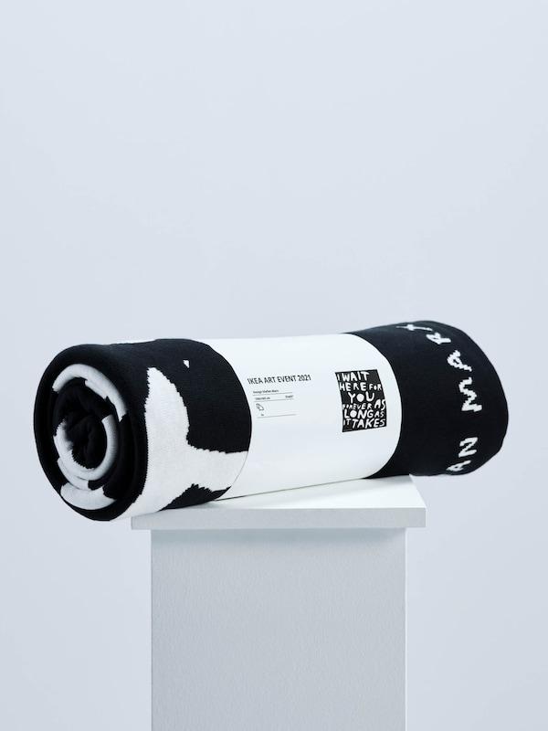 A Stefan Marx által az IKEA ART EVENT 2021 kollekcióhoz tervezett fekete-fehér takaró, fehér talapzaton.