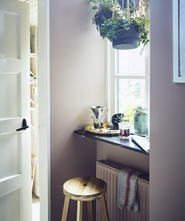 A stool and ledge in front of a large window with hanging plants and coffee-making equipment.