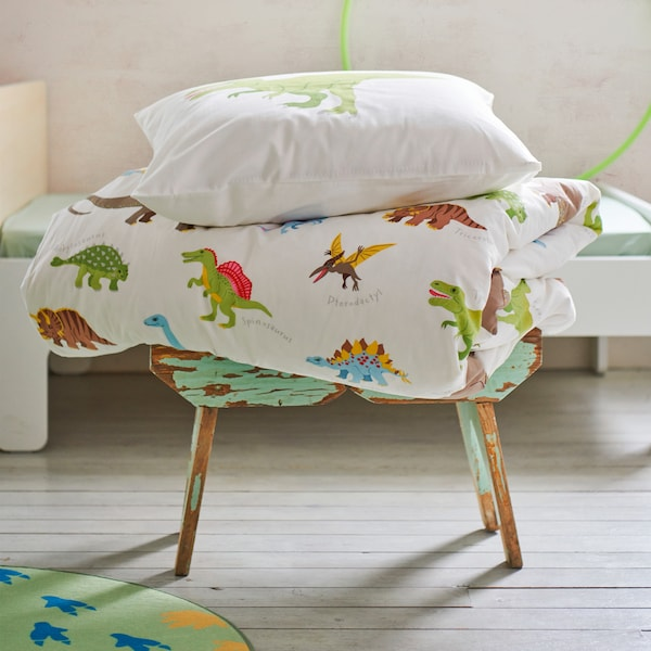 A stool with JÄTTELIK quilt cover and pillowcase with a colourful dinosaur print featuring brontosauruses to T-rexes.
