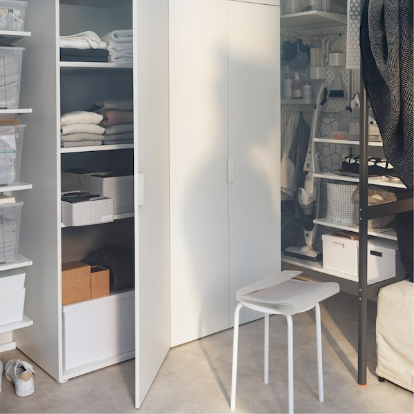 A storage area packed with boxes, shelves and an IKEA PLATSA storage unit filled with clothes and boxes.