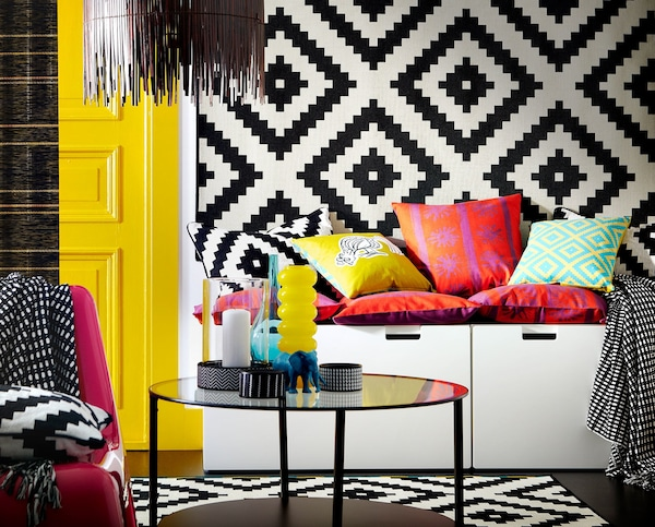 A storage bench with cushions on top for seating and a patterned rug hanging on a wall.