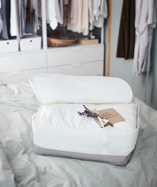 A storage case placed on a bed, the case holding a thick duvet along with a neatly written note and a few twigs of lavender.