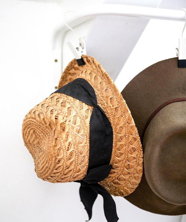 A straw hat hanging on a hook on a rail on a white wall.