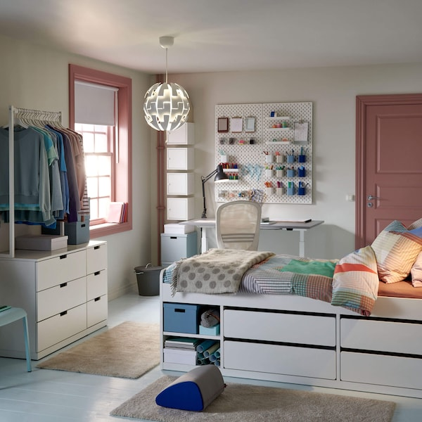 A student room with a bed in focus with integrated storage underneath and hanging clothes storage across the room.