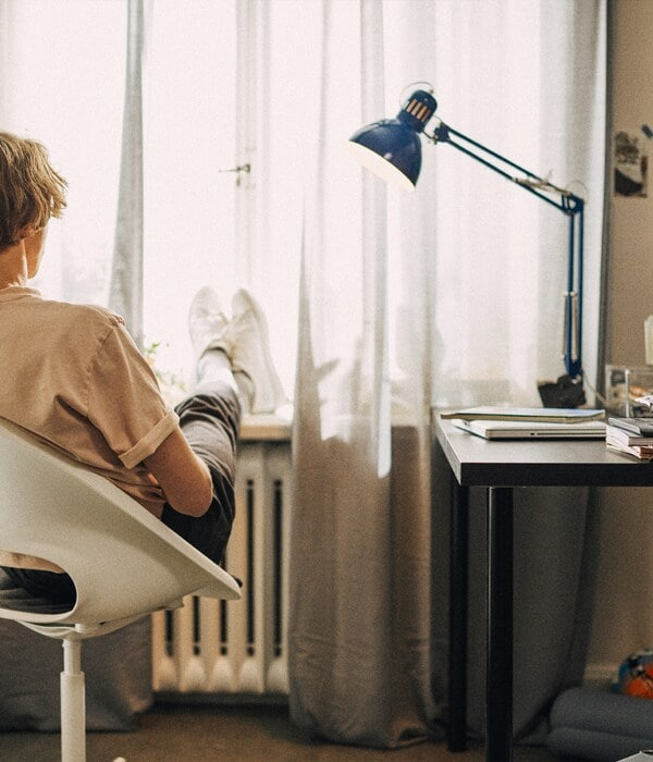 A student seated in a white chair relaxing next to a desk with a blue work lamp on it.