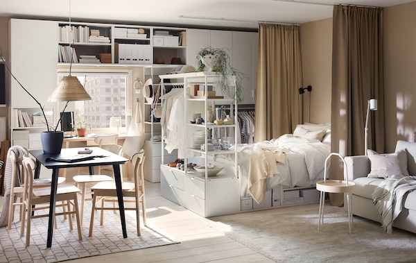 A studio flat with PLATSA storage combinations and bed frame in white, a dining table, a light grey sofa and beige curtains.