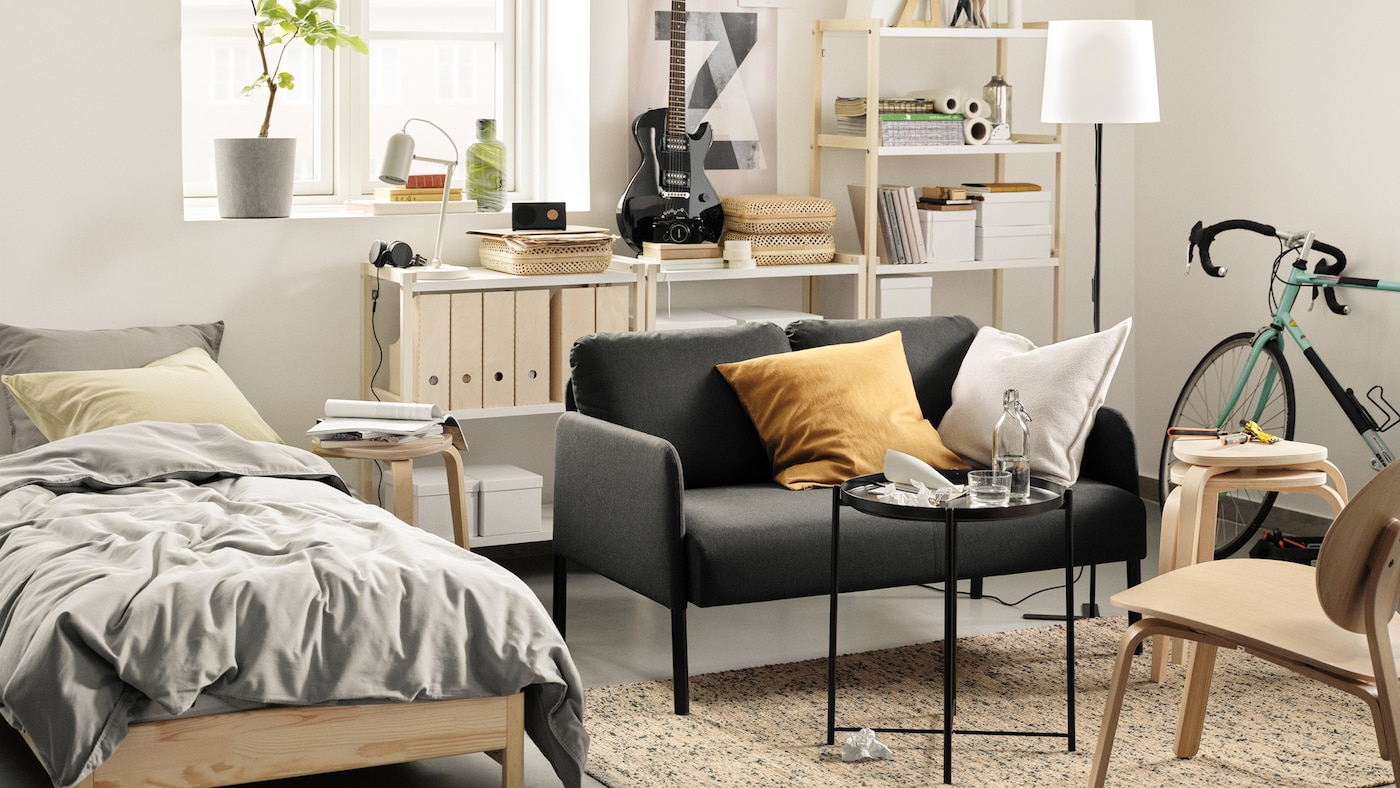 A studio room with a bed, GLOSTAD sofa and an open shelving unit against the wall. A small table is in front of the sofa.