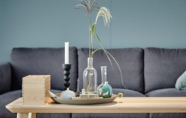 A stylish coffee table with a box and a tray holding vases, a candlestick and some ornaments.