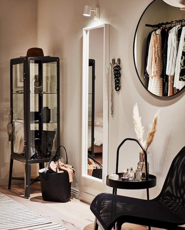 A stylish dressing corner with a white full-body mirror, a wall lamp, hooks with necklaces and a side table with perfumes.