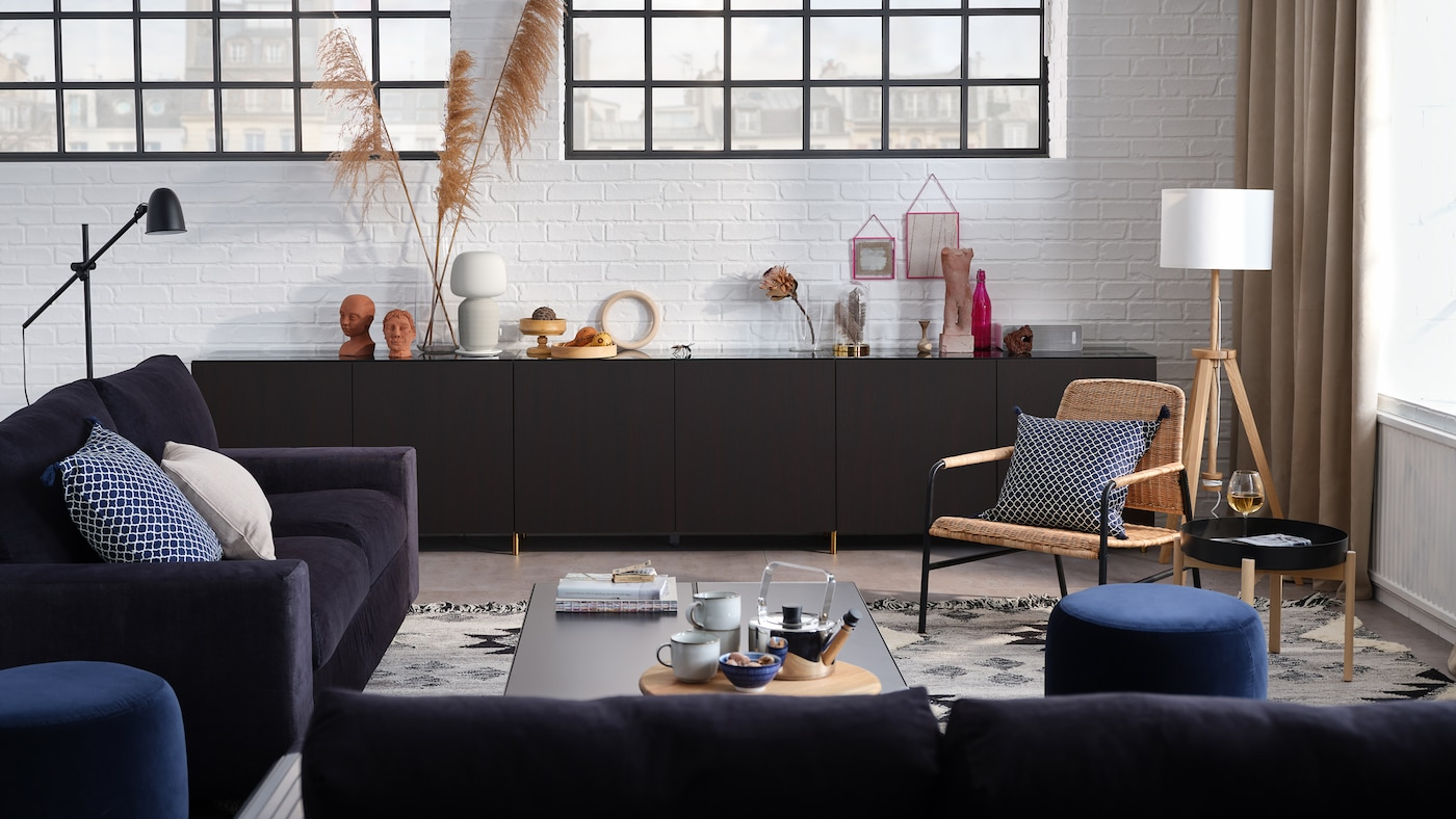 A stylish living room with a 3-seat sofa, a 2-seat sofa-bed, storage combination with doors, and an armchair.