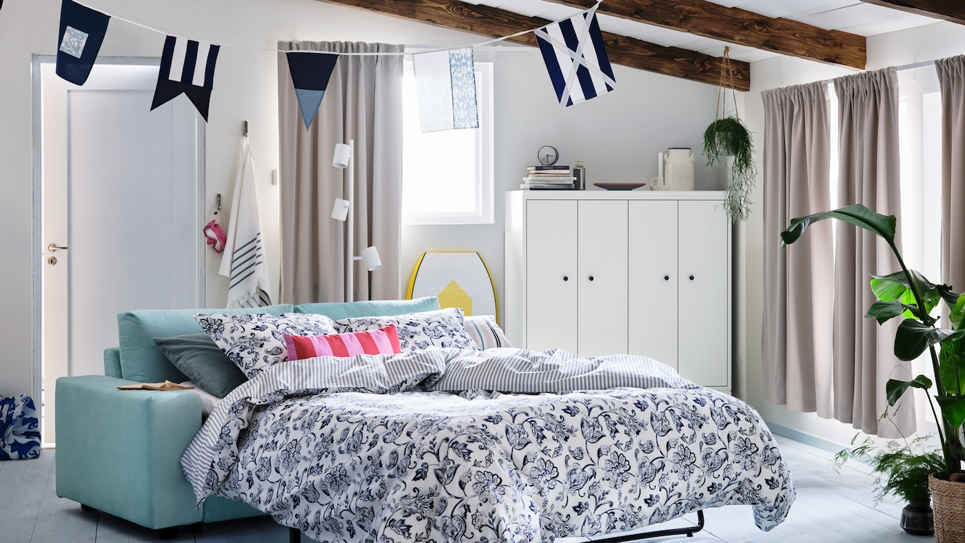 A summer house with windows dressed with room darkening curtains. A VIMLE two-seat sofa-bed made with JUNIMAGNOLIA bedding.