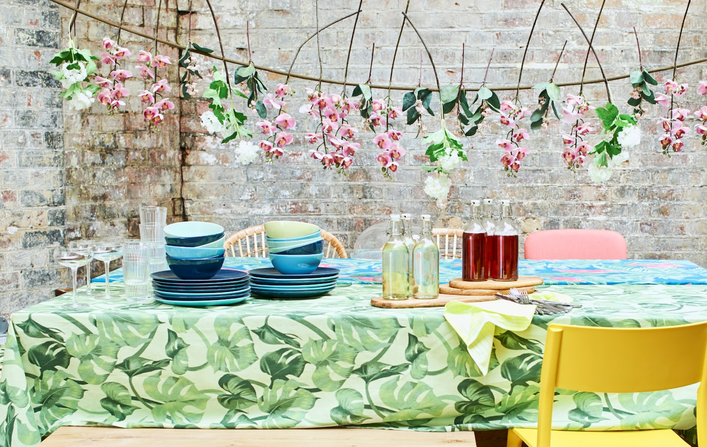 A summer party table with bright tablecloths, piles of blue crockery, mixed chairs and a garland of artificial flowers.