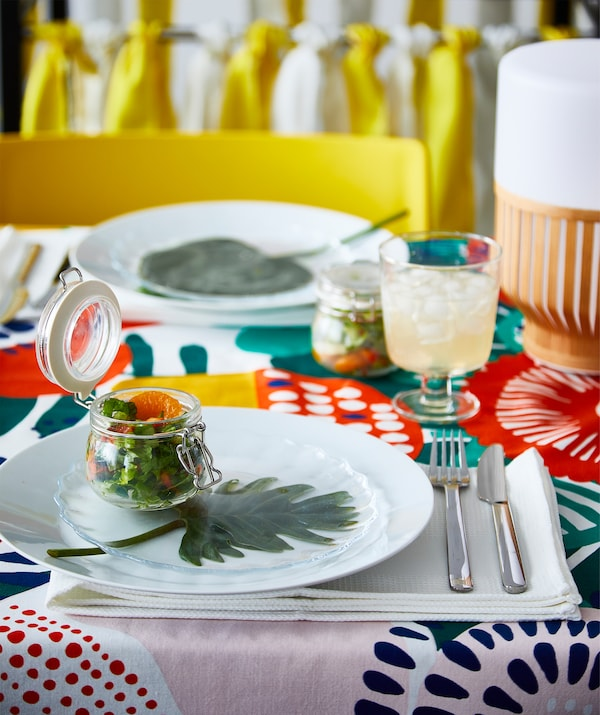A summer salad served in a clear glass IKEA KORKEN jar at a colourful party.