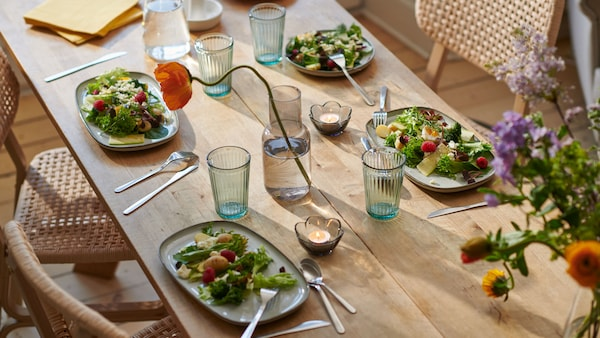 A summer table setting with tea lights, blue glasses, and rectangular plates filled with salad.