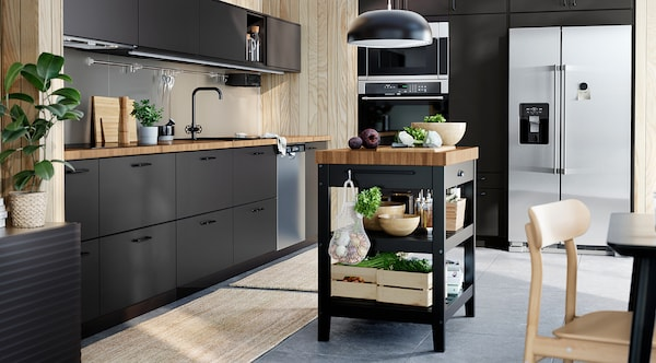 A sunlit kitchen with black KUNGSBACKA recyled plastic kitchen cabinets.