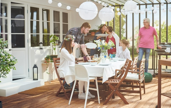 A sunlit roofed terrace with people around a table decorated with flowers, hanging lanterns and a small Swedish flag.