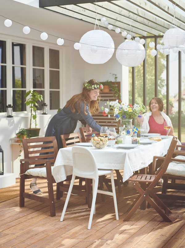 A sunlit roofed terrace with two people around a group of ÄPPLARÖ table and chairs, the table set and decorated for a party.
