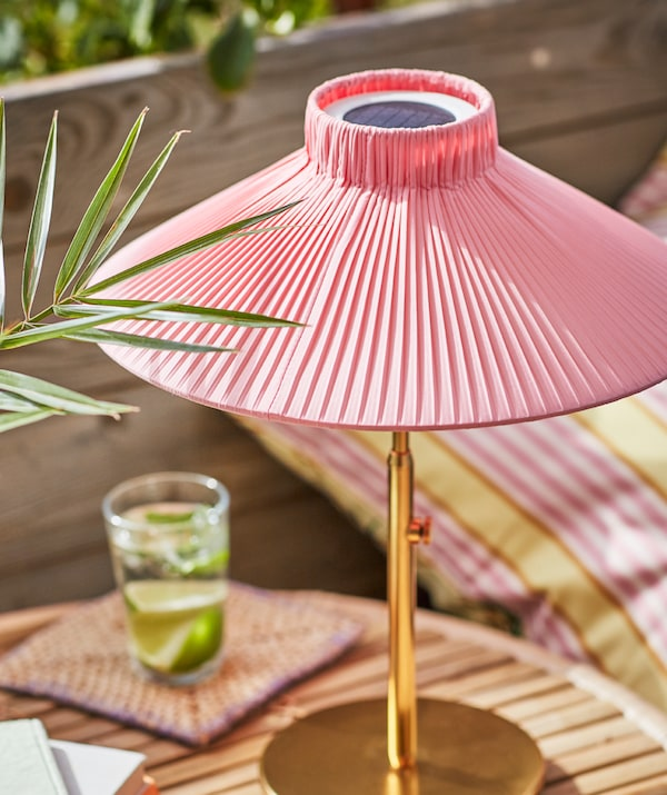 A sunlit SOLVINDEN solar-powered table lamp standing on a small table together with a glass holding a drink and lime wedges.