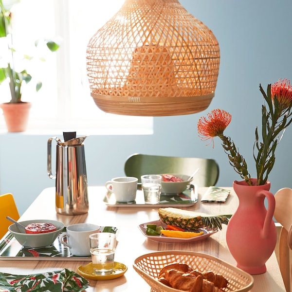 A sunlit table set for teatime with brightly patterned accessories.
