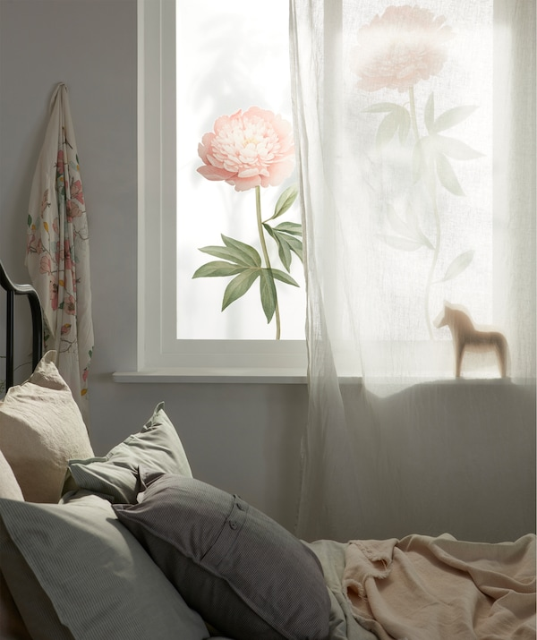 A sunlit window that's partly covered by a sheer curtain and decorated with large floral deco stickers, in a bedroom setting.
