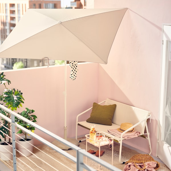 A sunny balcony with a white INGMARSÖ sofa on it under a white TVETÖ parasol. Lush green leafy plants are beside it.