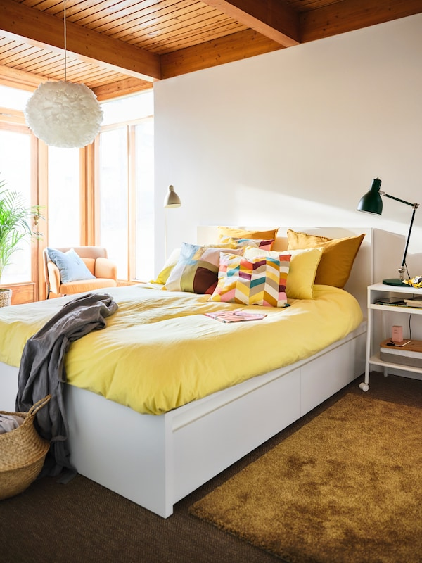 A sunny, bright bedroom with a white MALM bed dressed with a bright yellow bedcover and HANNELISE pillows at its centre.